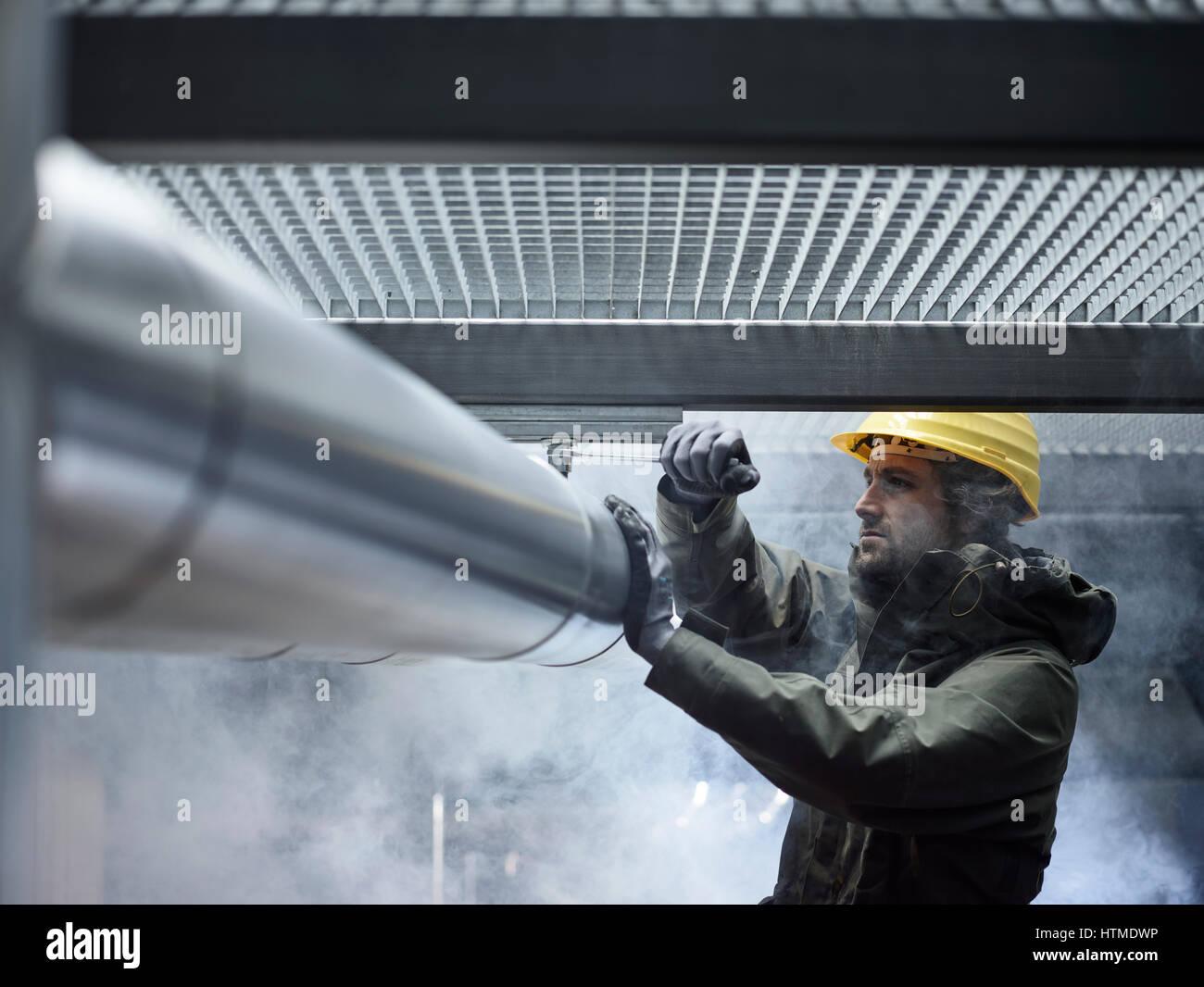 Mechanic, technician fixing mount of a pipeline, Austria - Stock Image