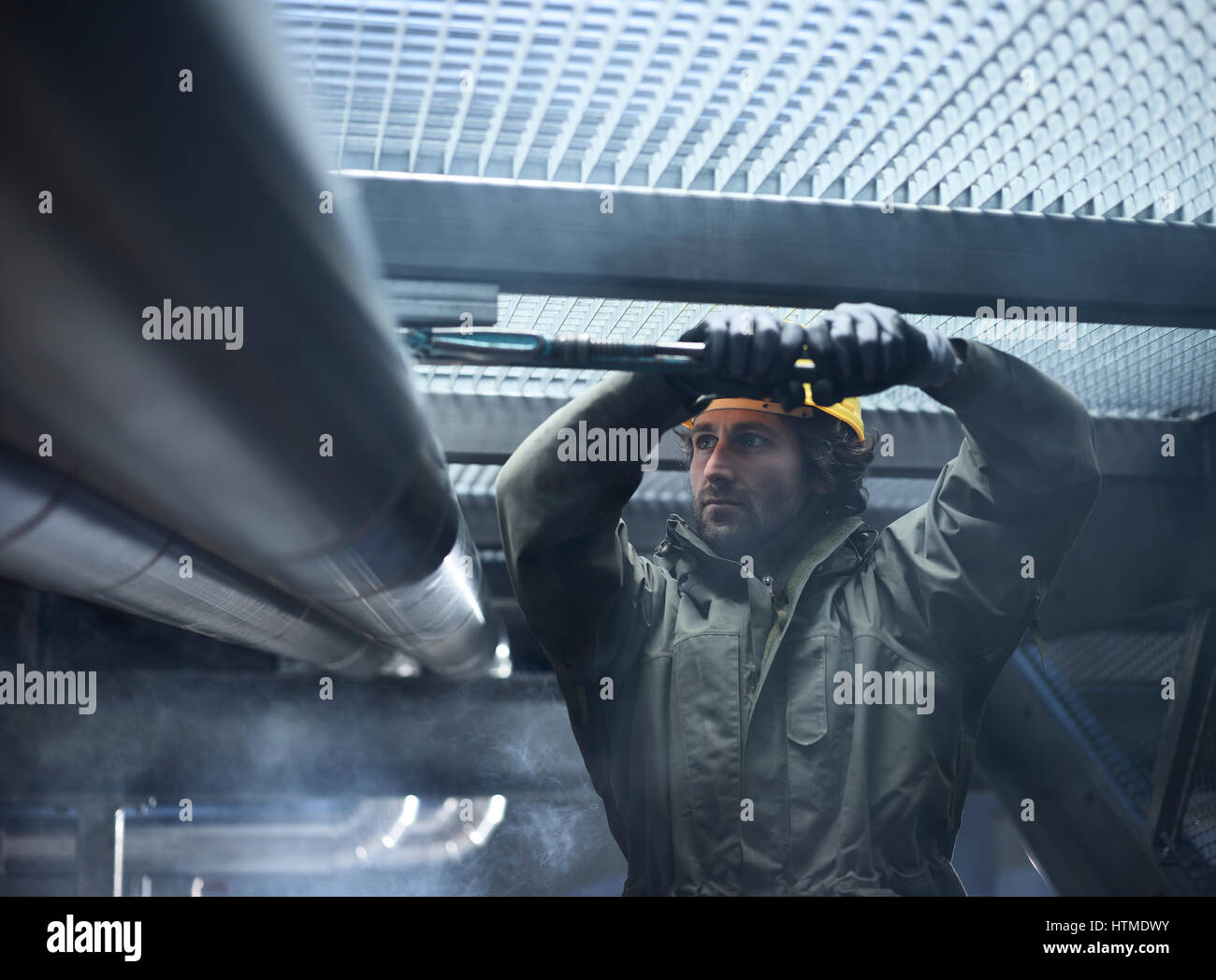 Mechanic, technician fixing mount of a pipeline, Austria - Stock Image