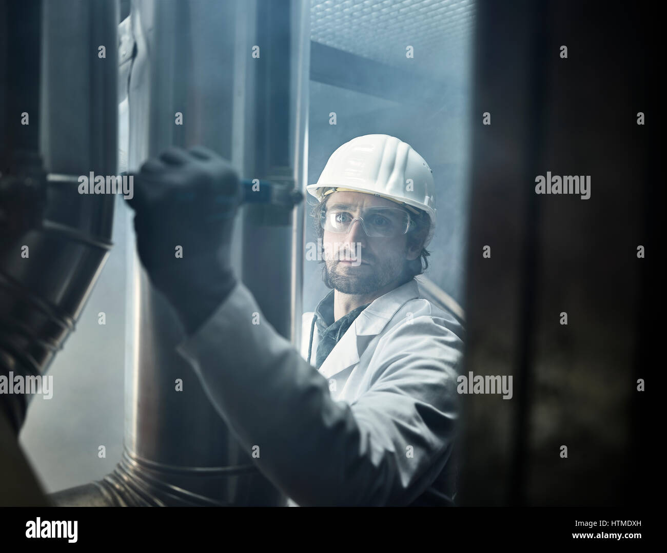 Mechanic with white helmet and lab coat moving a lever of a refrigerant line, Austria - Stock Image