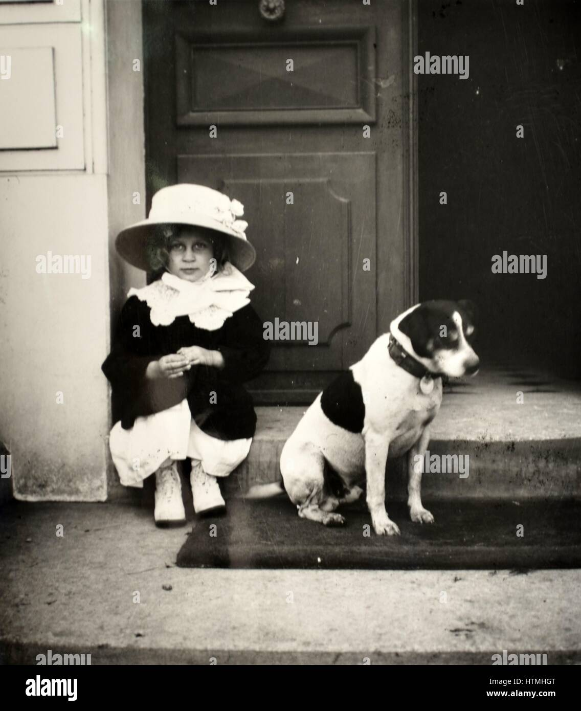 French girl photographed in a doorway with her pet dog, circa 1896 - Stock Image