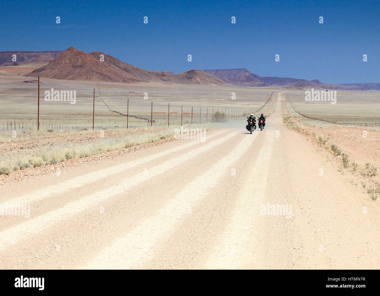 Two motorbikes driving fast on long straight desert road. - Stock Image
