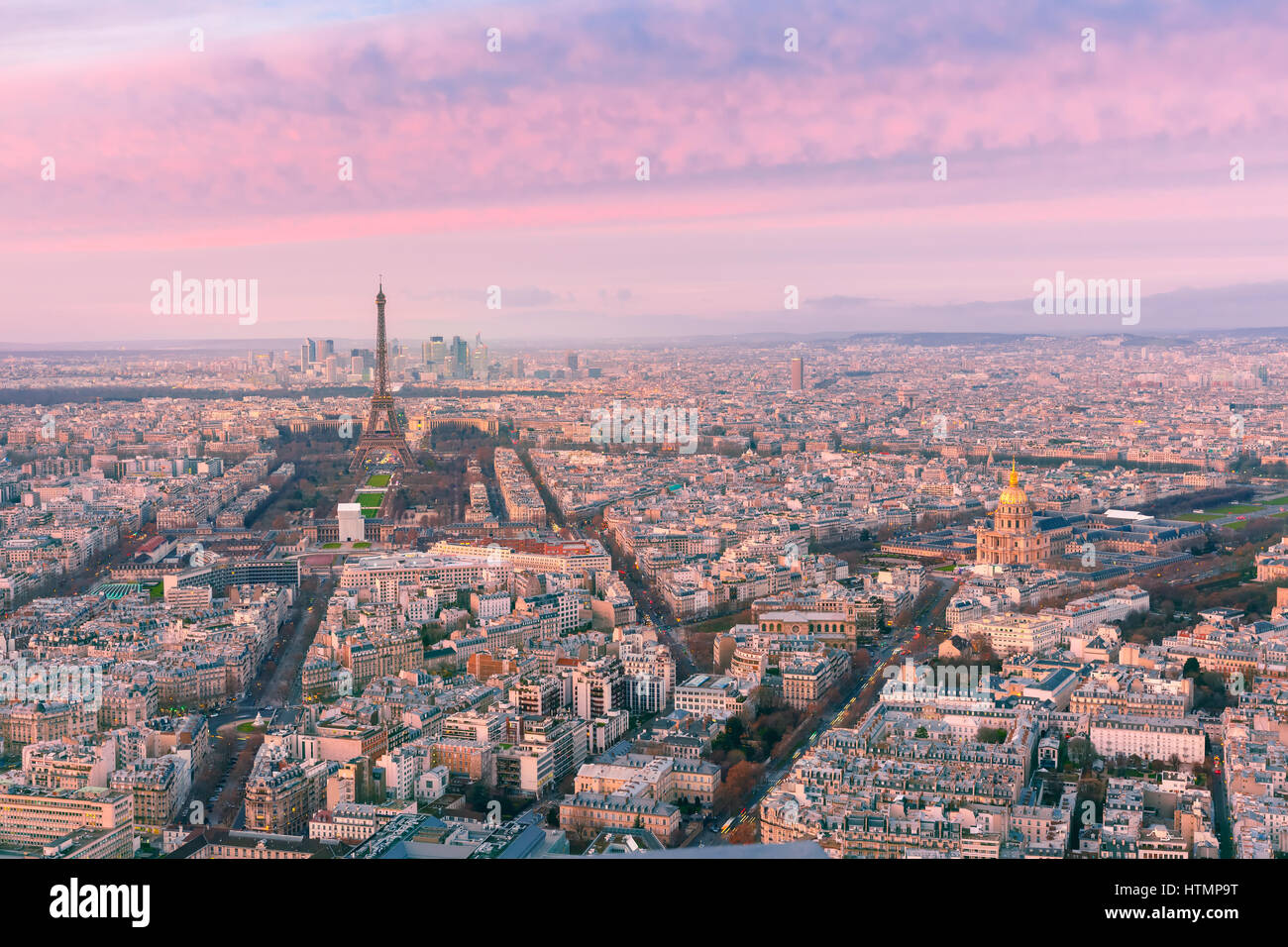 Aerial panoramic view of Paris skyline with Eiffel Tower, Les Invalides and business district of Defense at pink - Stock Image