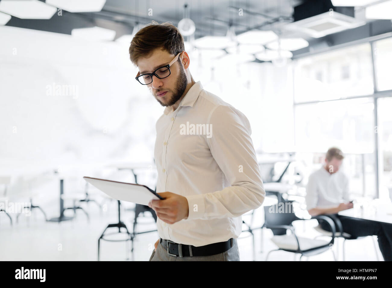 Confident businessman wearing shirt and glasses  using tablet - Stock Image