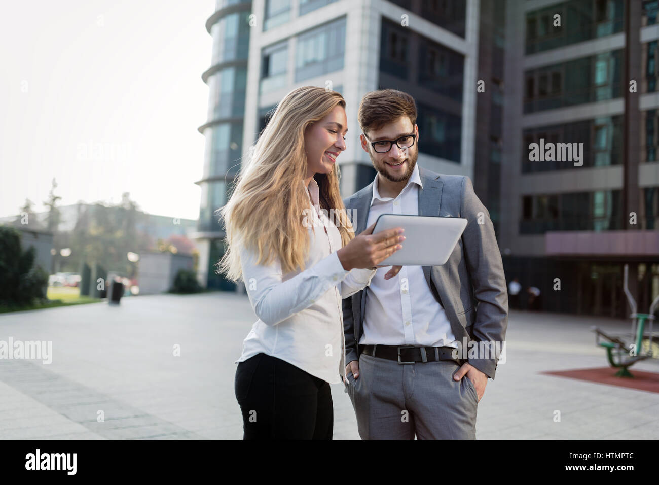 Business people walking outdoors and using phones tablets Stock Photo