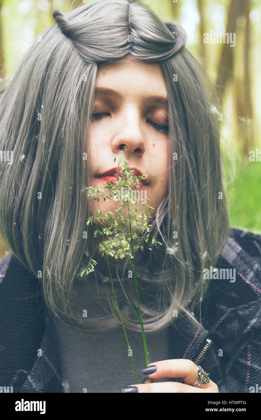 Young woman with grey hair in a forest - Stock Image
