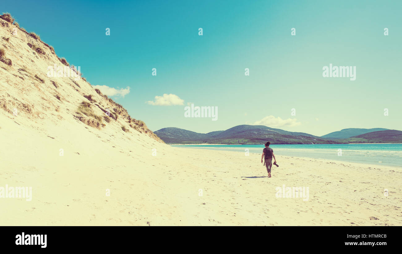 Young male photographer with dreadlocks at a sunny white sand beach with high sand dunes, Luskentyre, Isle of Harris, - Stock Image