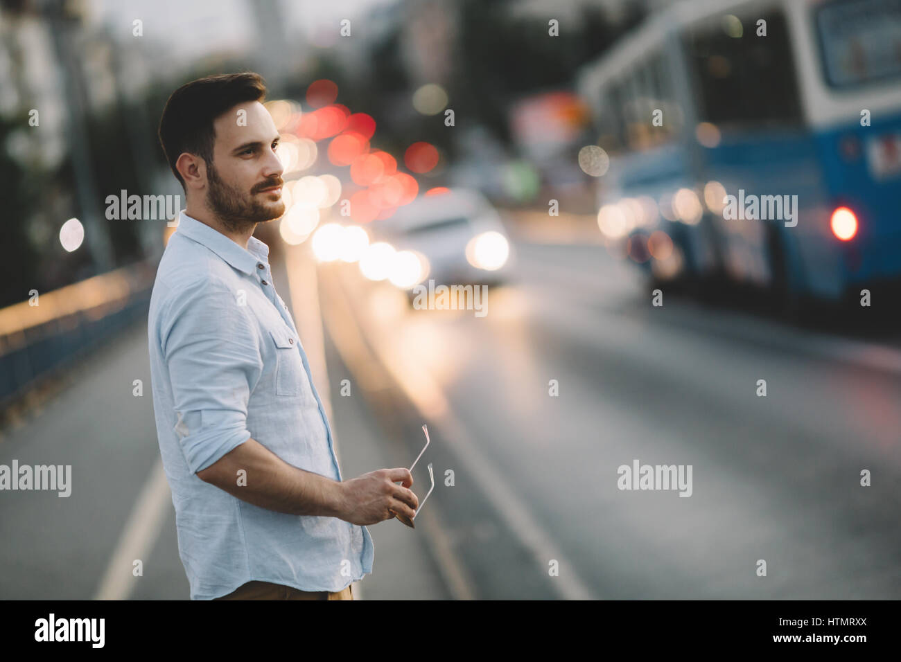 Aided by neon and city lights a male is walking home in city - Stock Image