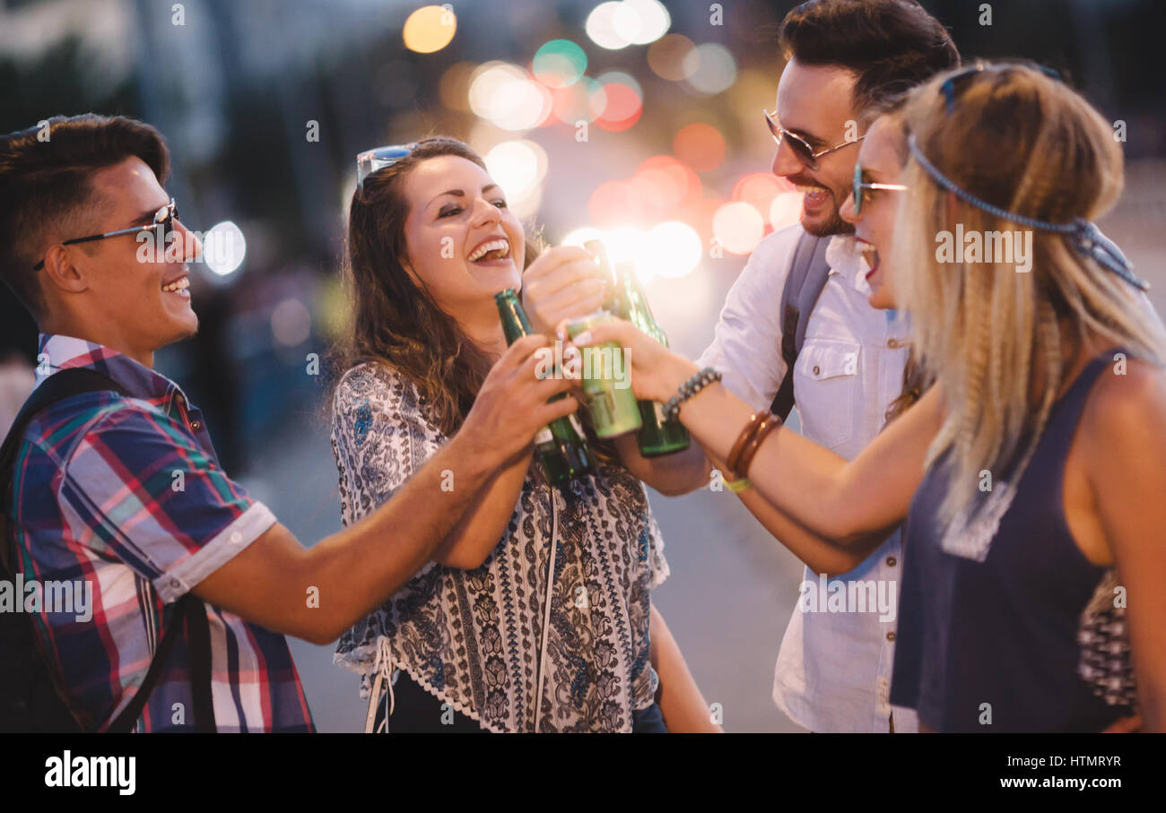 Happy friends drinking alcohol outdoors and partying before festival - Stock Image