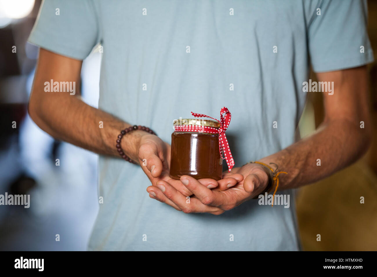 Mid-section of man holding a jar of jam in market - Stock Image