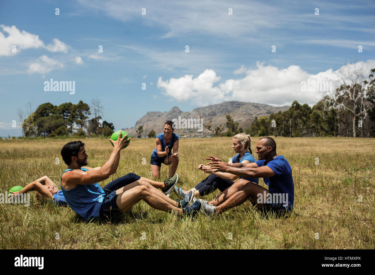 Fit people performing core exercise in bootcamp - Stock Image