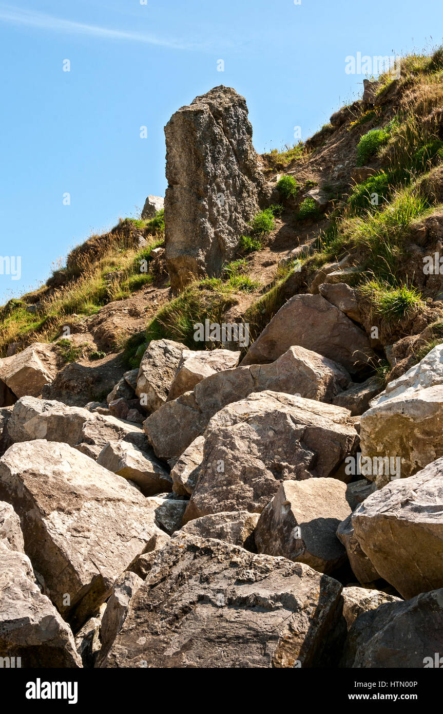 Large sections of fractured rocks lie at the foot of a steeply sloping cliff edge from which a weathered stone pillar - Stock Image