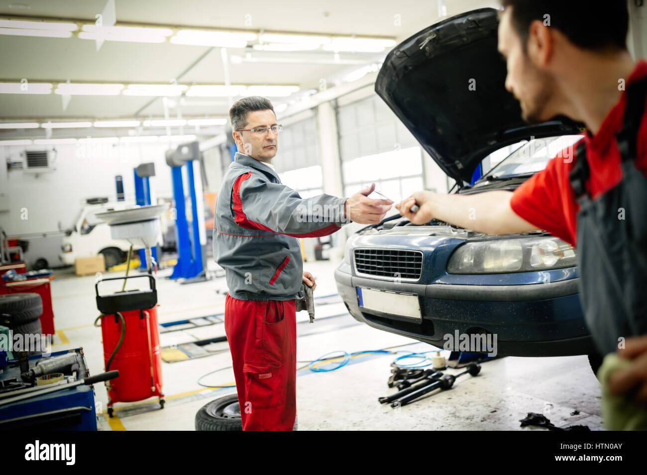 Car mechanic working as a team fixing car - Stock Image