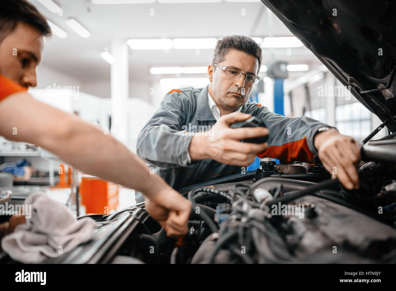 Car mechanics working on car maintenance - Stock Image