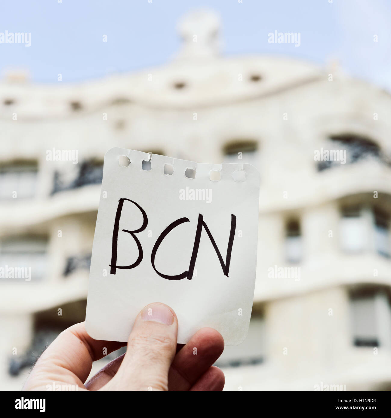 closeup of the hand of a young caucasian man holding a note with the word BCN, for Barcelona, written in it, in - Stock Image
