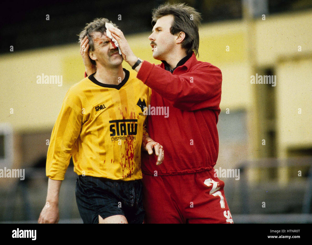 Footballer Barry Powell covered in blood is helped off the Molineux pitch by Wolverhampton Wanderers physiotherapist - Stock Image