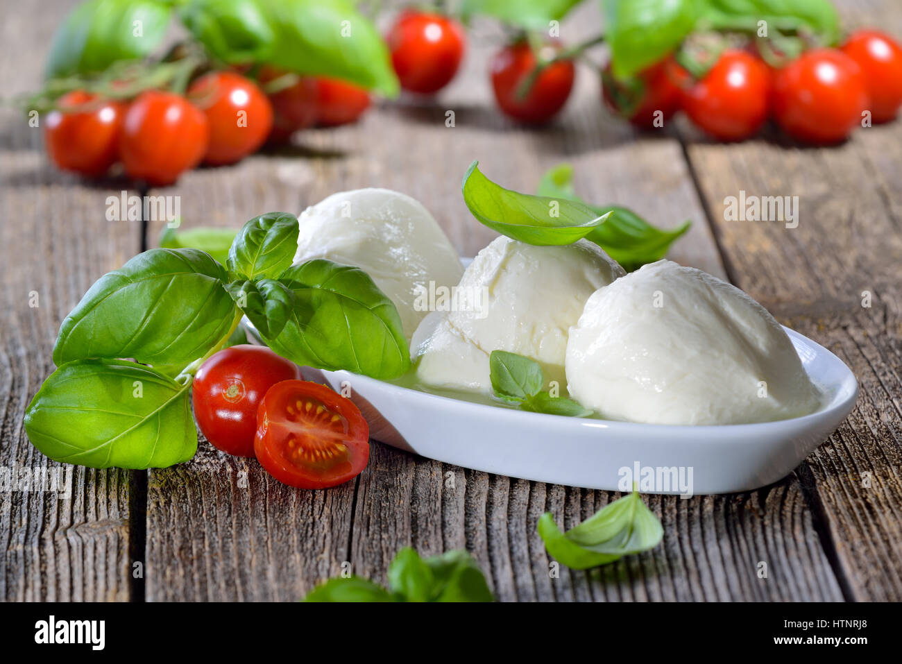 Three mozzarella cheese balls in a white bowl, garnished with cherry tomatoes and basil Stock Photo
