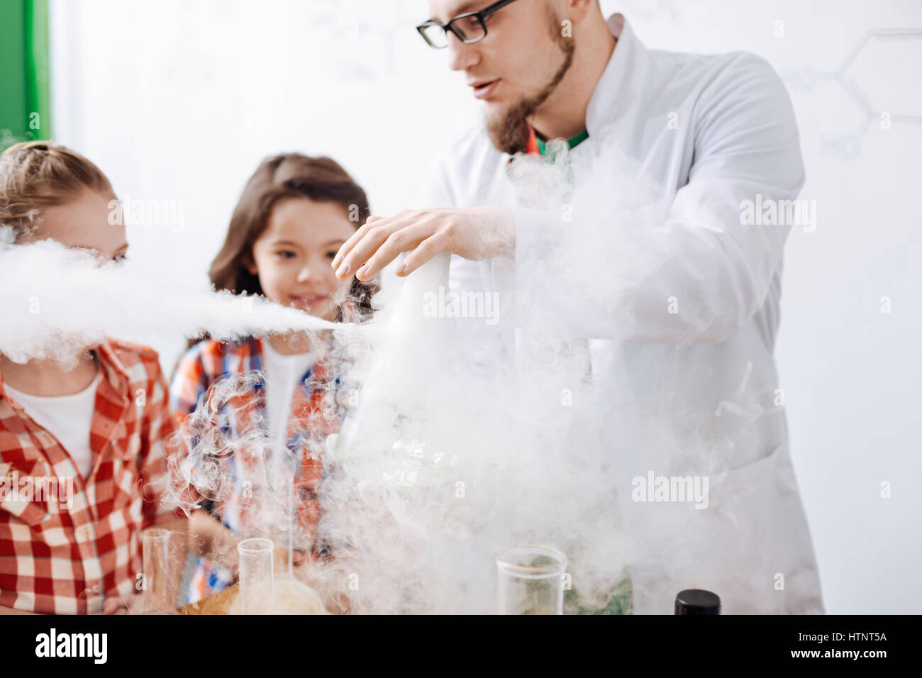 Interaction of chemical reagents. Serious nice experienced scientist performing an experiment and being surrounded - Stock Image
