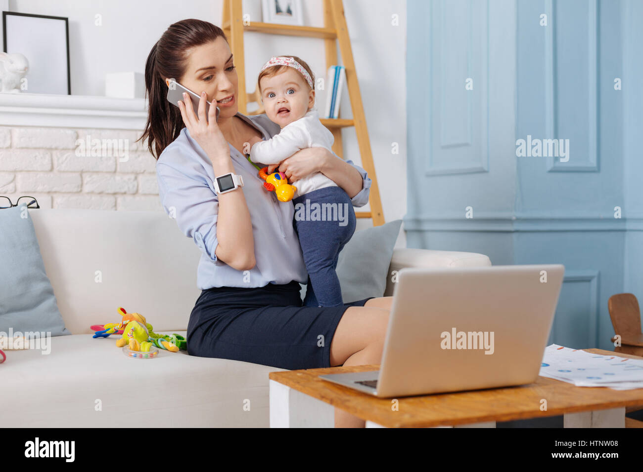 Handling everything. Capable independent modern woman negotiating on new terms for her business while holding her - Stock Image