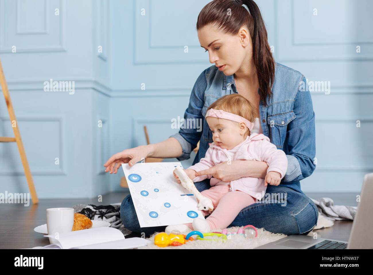 With a little helper. Graceful focused inventive woman thinking about new projects while analyzing data and trying - Stock Image