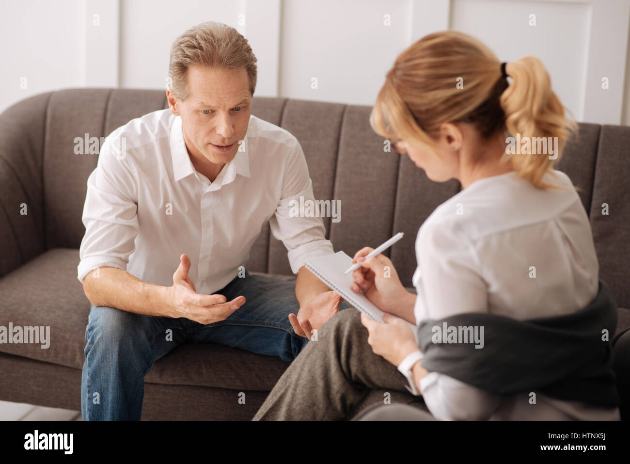 Professional help. Nice handsome pleasant man sitting comfortable on the sofa and sharing his concerns with a psychologist - Stock Image