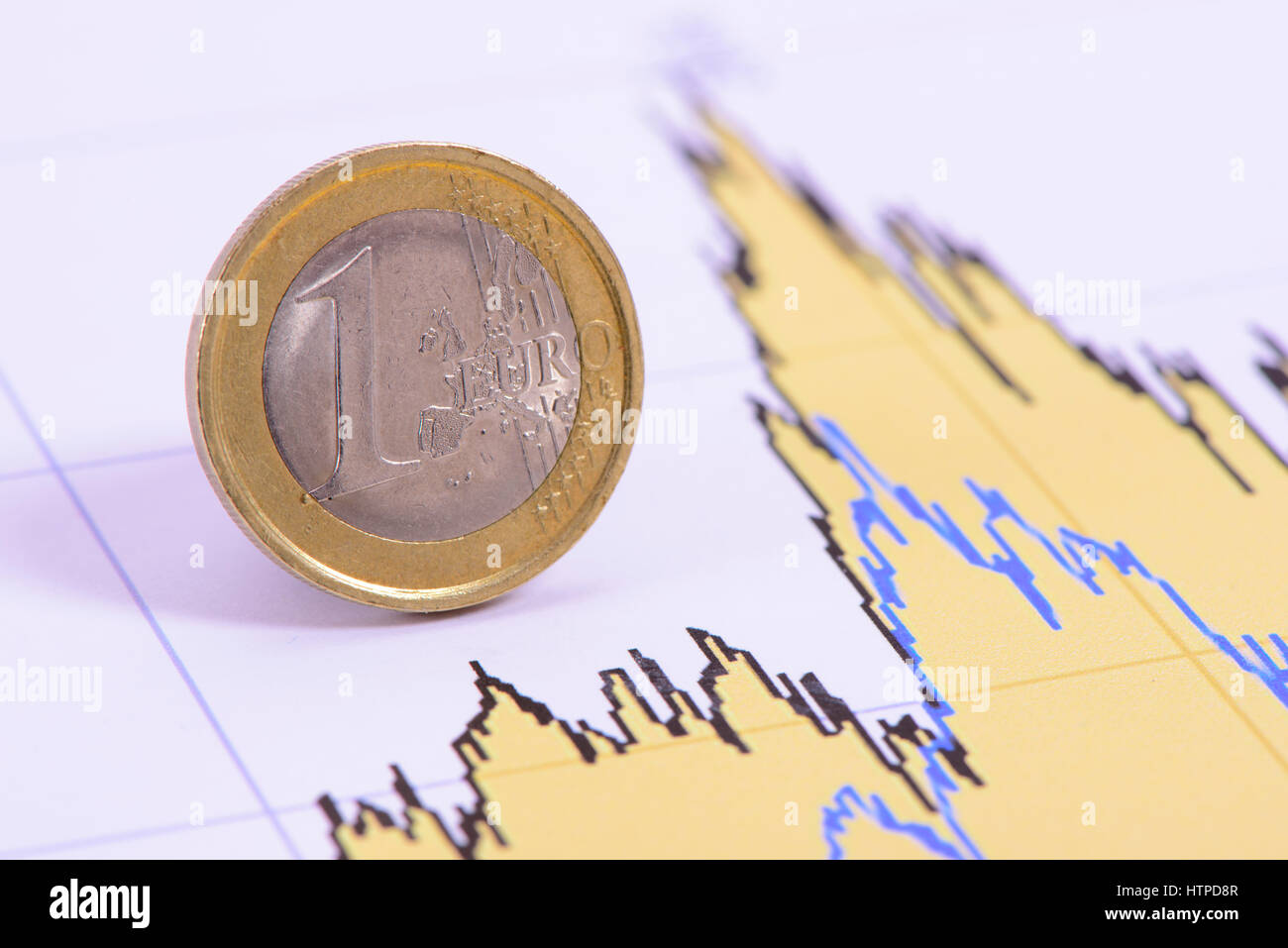 Euro coin of european currency laying in chart of exchange market - Stock Image