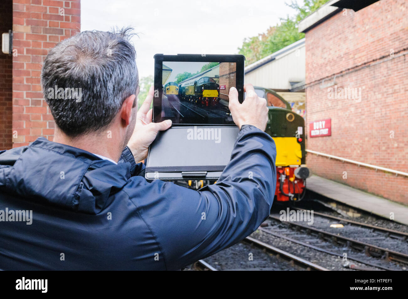 A rail enthusiast taking a picture of class 37 and class 40 locos at Bury on the East Lancs Railway - Stock Image