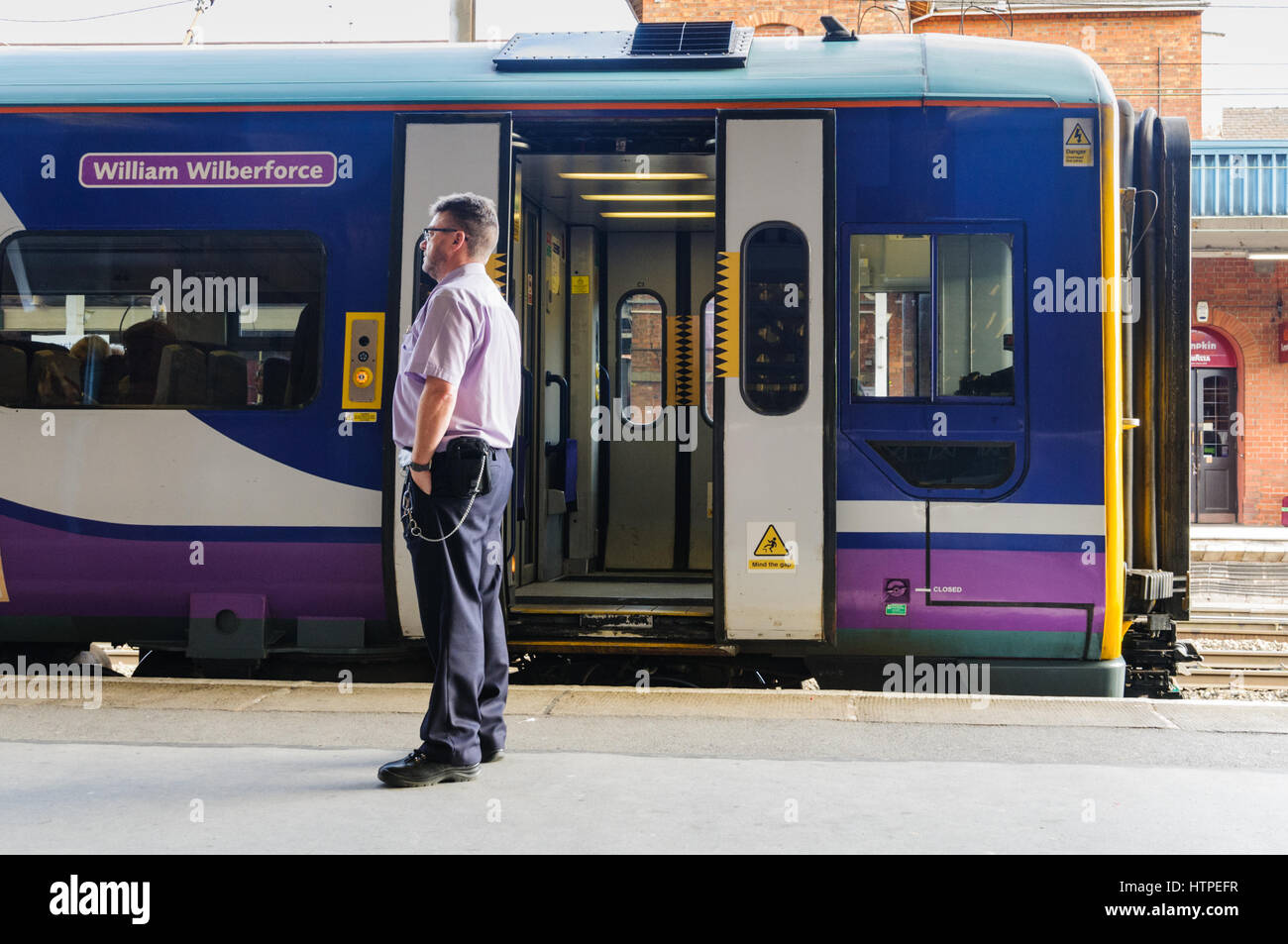 Train guard waiting at the side of his Transpennine Express Train at Doncaster station Stock Photo