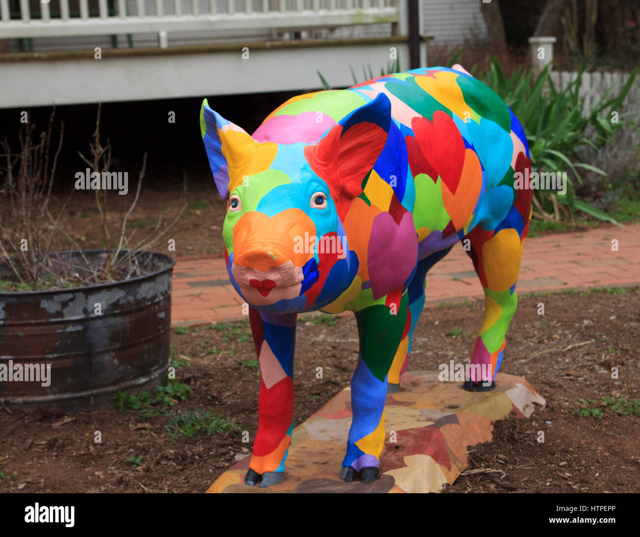 artistic Pig statue with painted hearts - Stock Image
