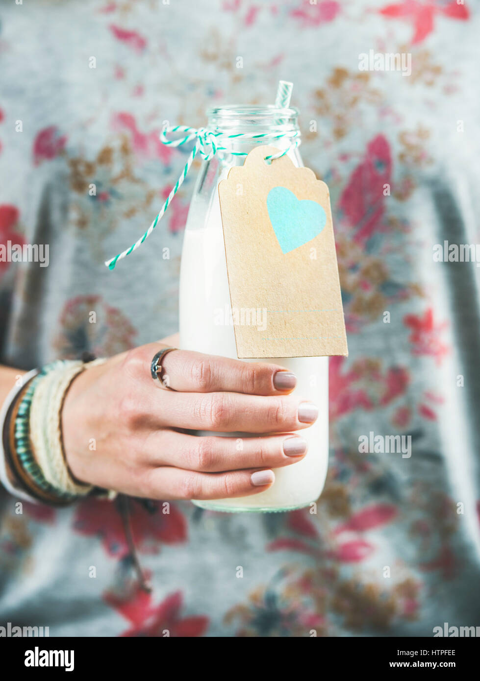 Young woman in grey t-shirt with floral pattern holding bottle of dairy-free almond milk in her hand. Clean eating, - Stock Image