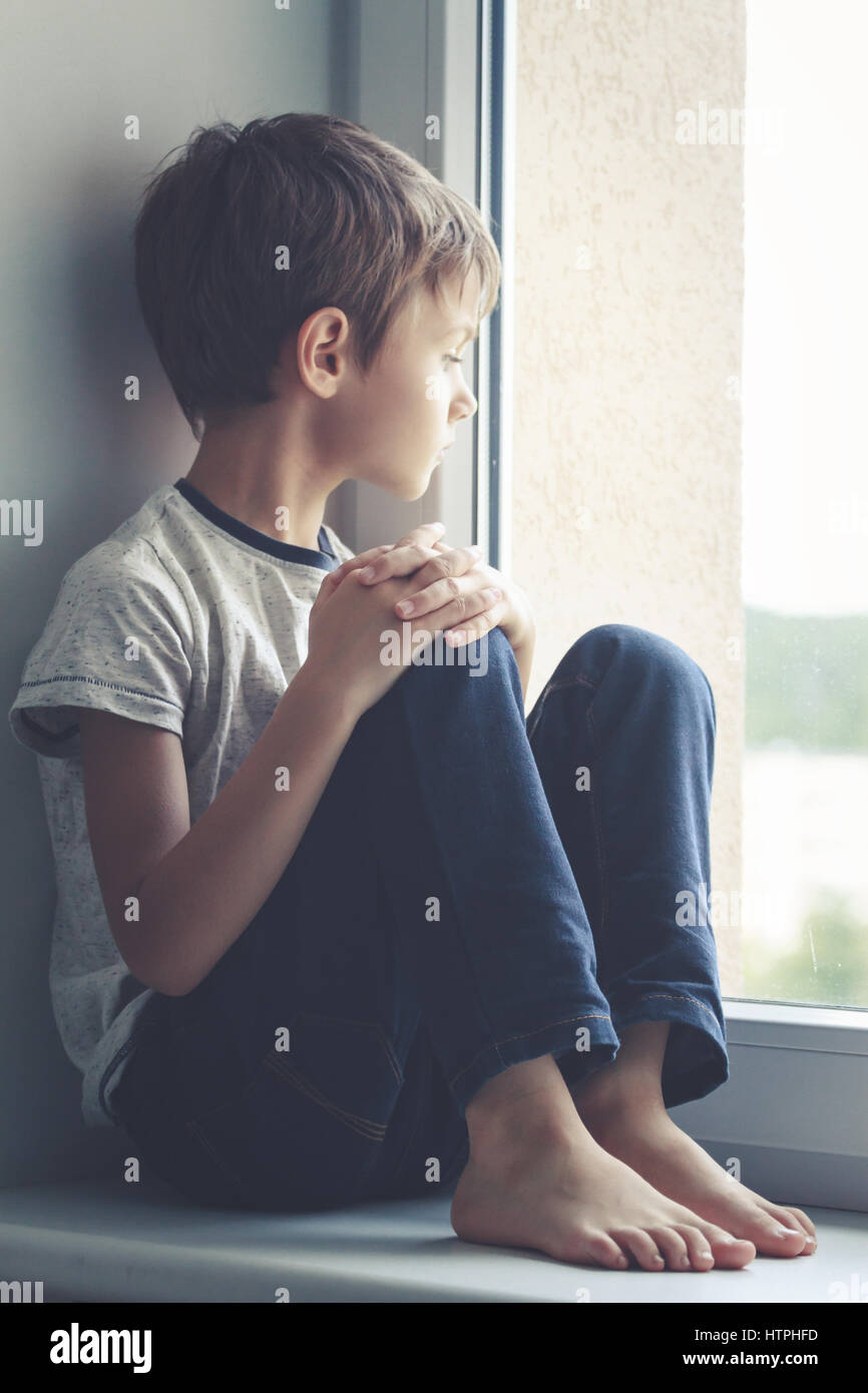 Sad child sitting on window shield and looking out the window - Stock Image