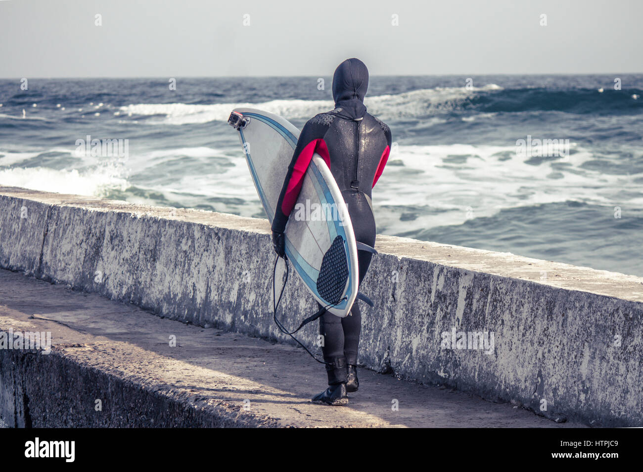 Surfer walks  into water wearing a wetsuit in winter. Cold surfing. Wave splash. waterproof suit. He has action Stock Photo