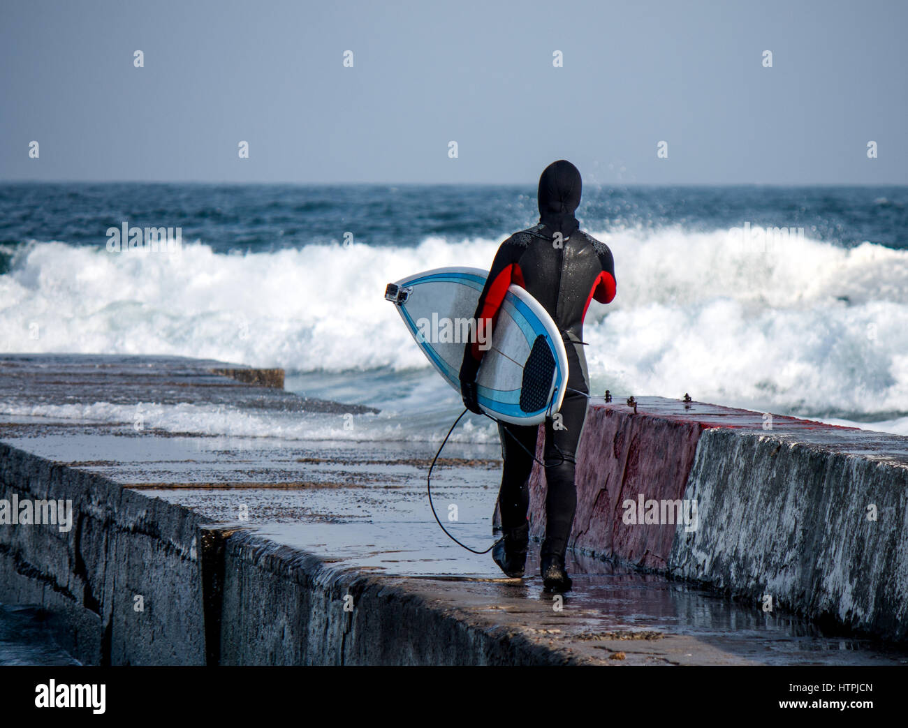 Surfer walks into water wearing a wetsuit in winter. Cold surfing. Wave splash. waterproof suit Stock Photo
