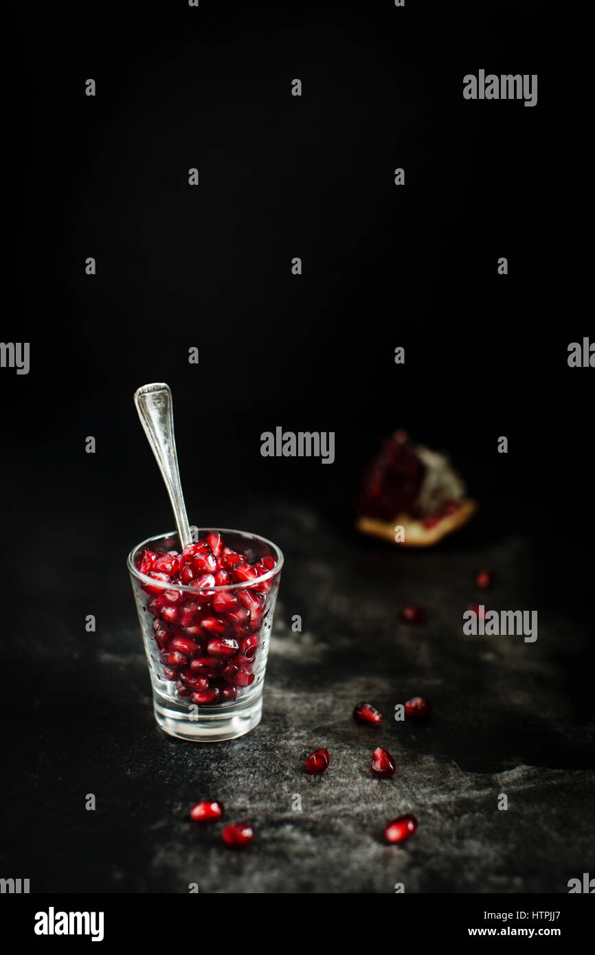 Fresh and juicy pomegranate seends on a dark background - Stock Image