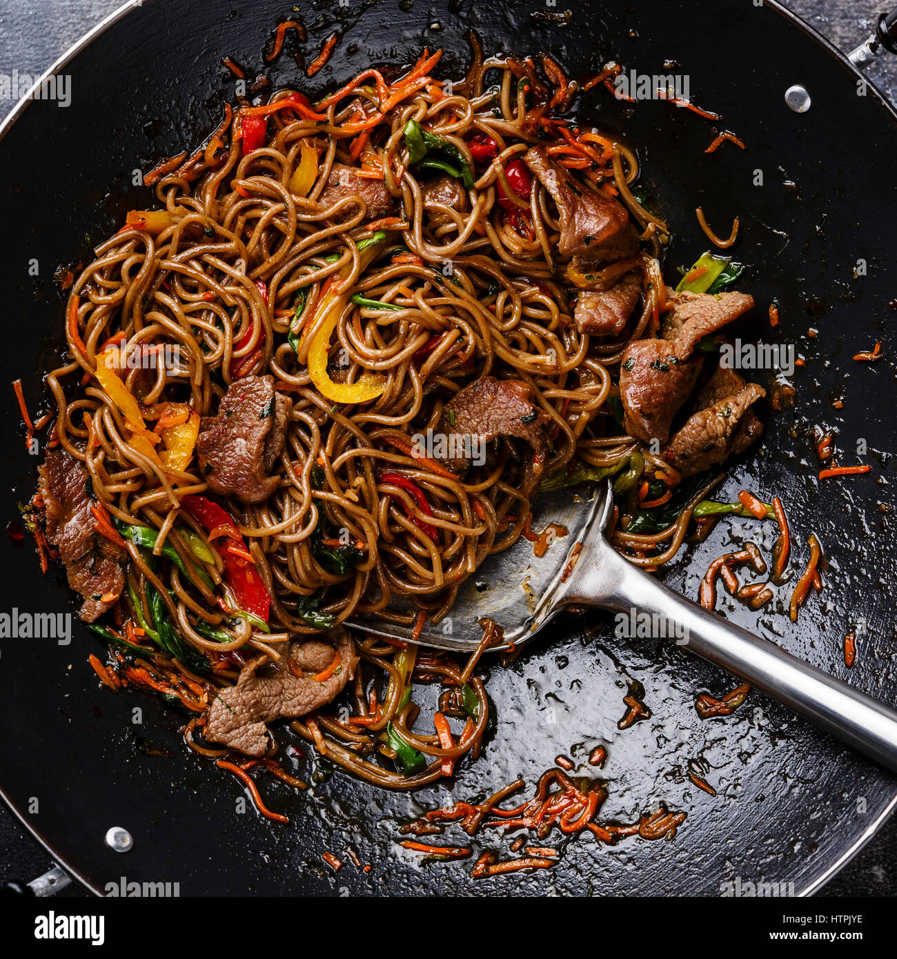 Stir fry soba noodles with beef and vegetables in wok pan close up - Stock Image