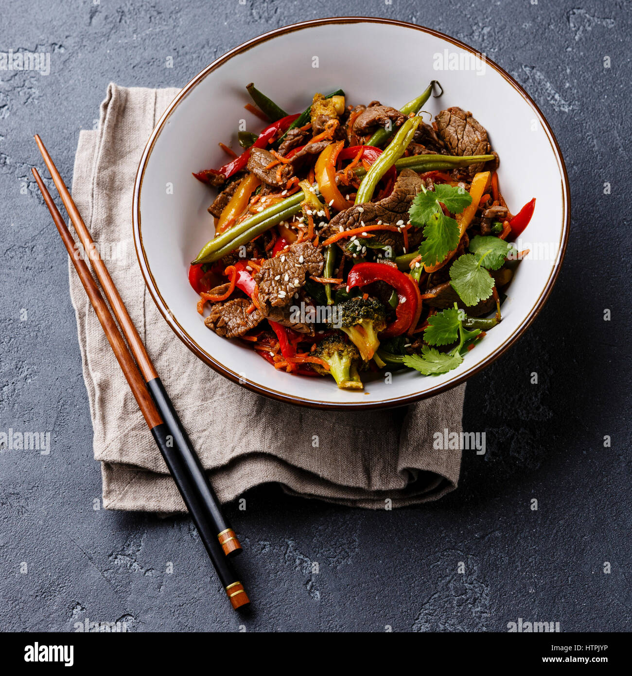 Szechuan beef stir fry with vegetables in bowl on dark stone background - Stock Image