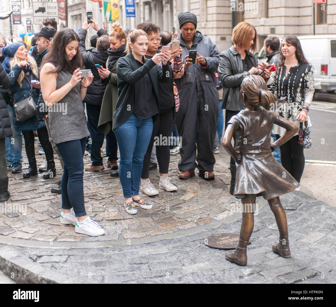 "The bronze statue, ""The Fearless Girl"" by the artist Kristen Visbal attracted attention at Bowling Green Park in Stock Photo"