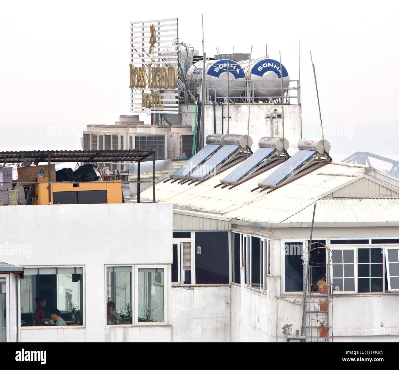 Solar hot water heaters with holding tanks installed on rooftop,  Boss Legend Hotel, high rise. - Stock Image