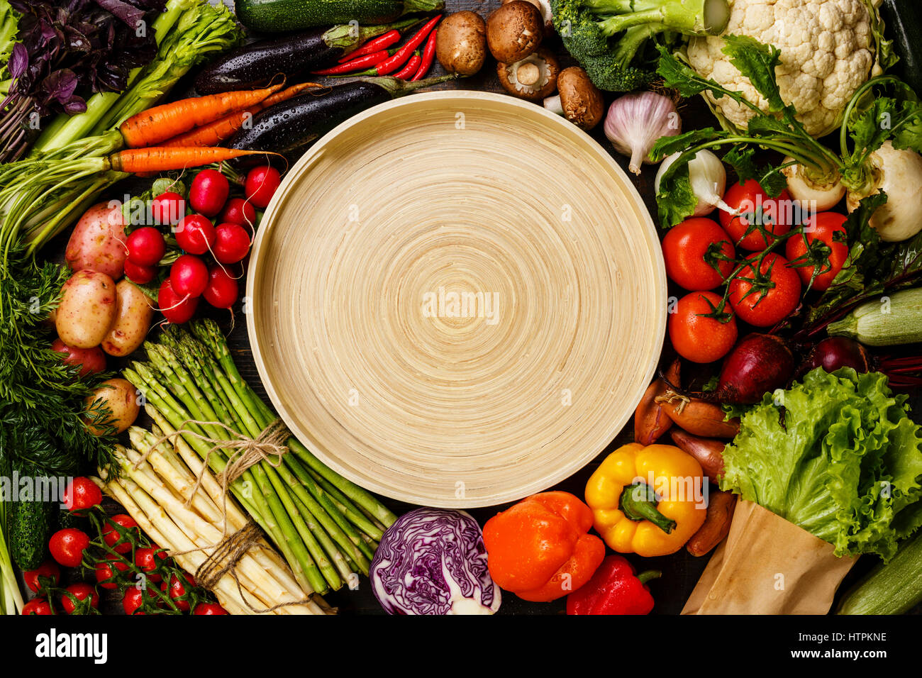 Fresh vegetables around round bamboo tray copy space - Stock Image
