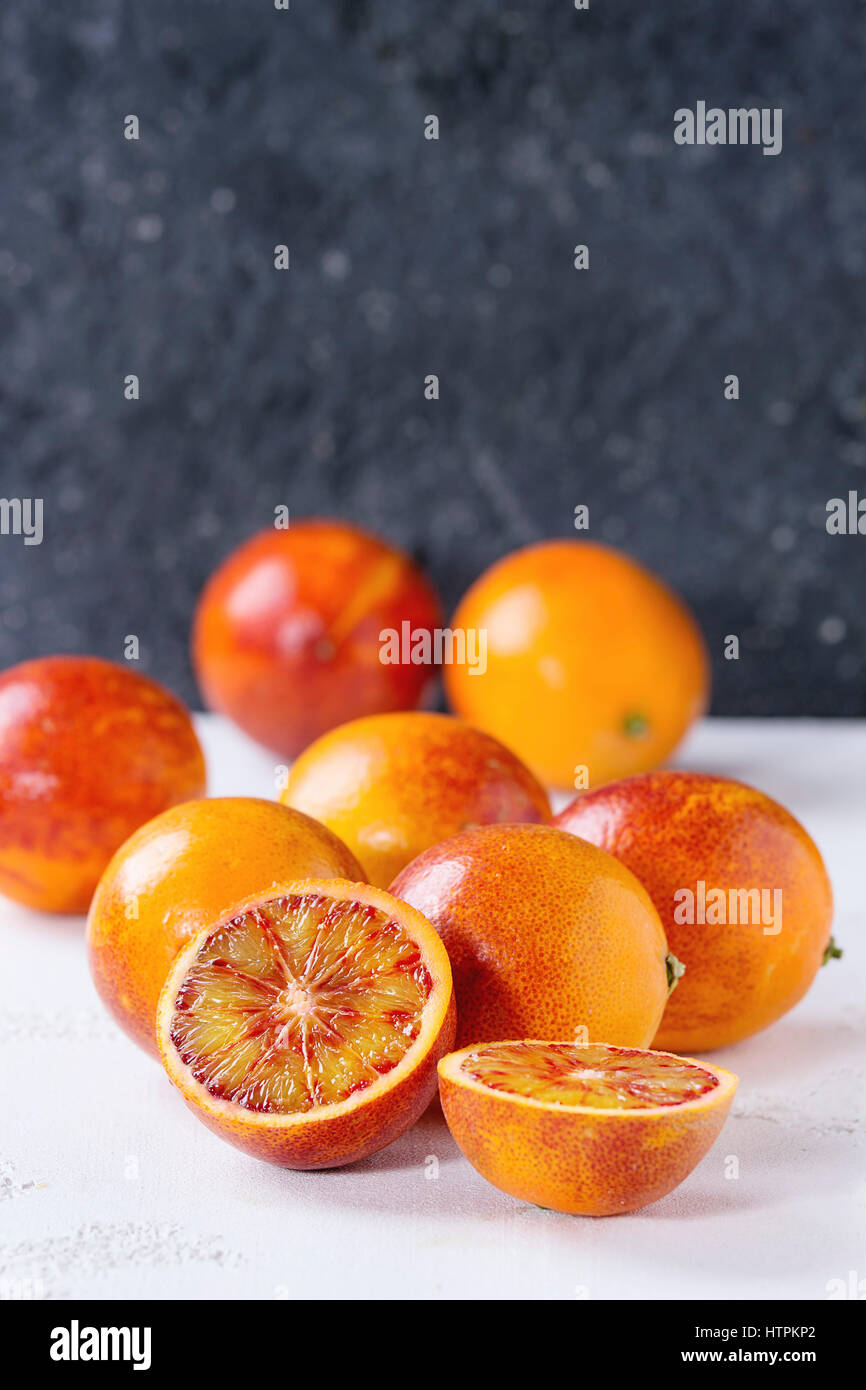 Sliced and whole ripe juicy Sicilian Blood oranges fruits over white and gray concrete texture background. Copy - Stock Image