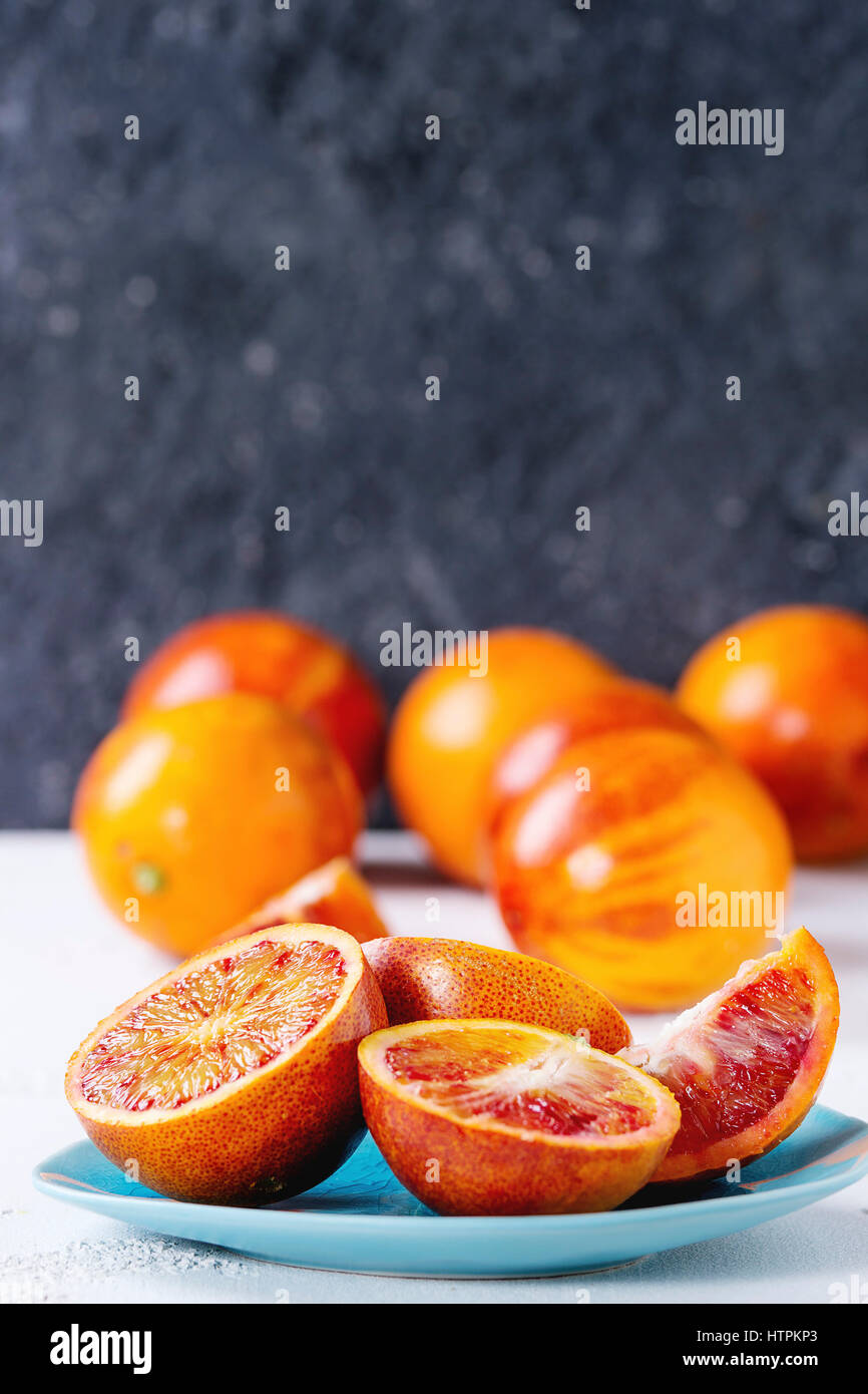 Sliced and whole ripe juicy Sicilian Blood oranges fruits on ceramic plate over white and gray concrete texture - Stock Image
