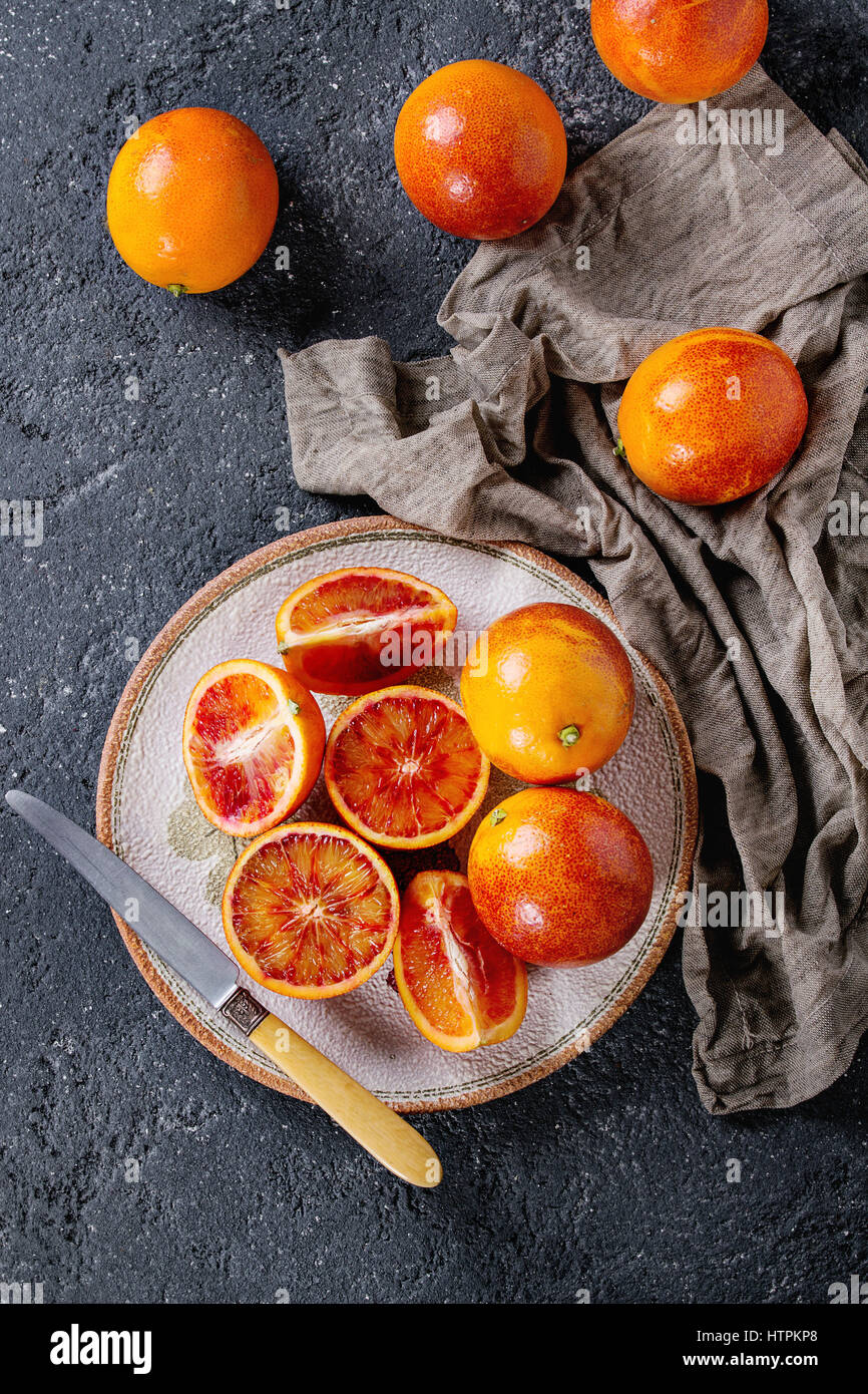 Sliced and whole ripe juicy Sicilian Blood oranges fruits with knife, sackcloth rag on ceramic plate over black - Stock Image