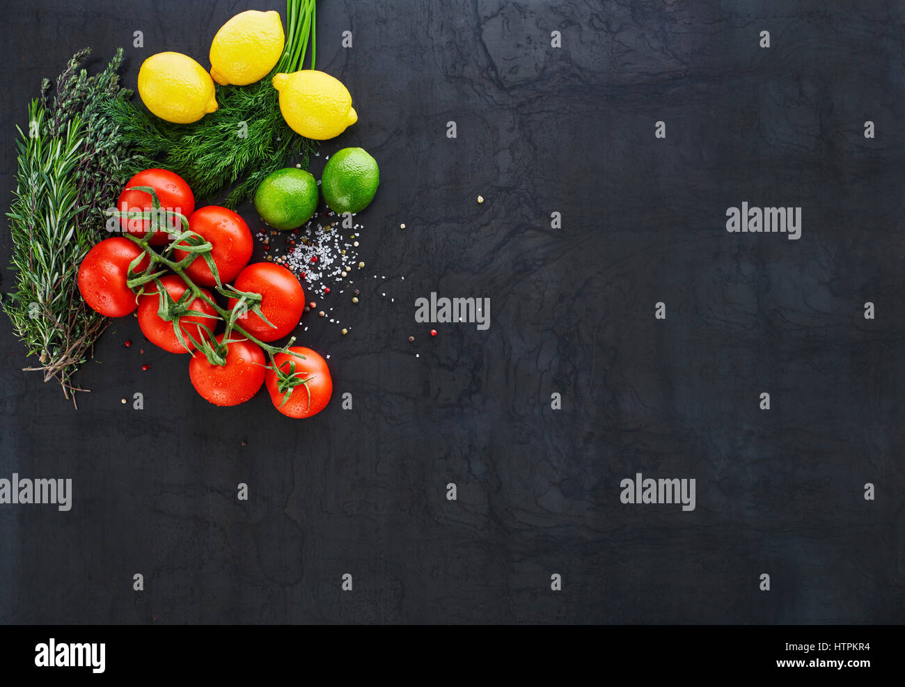 black rustic tabletop with vine of tomatoes, herbs, limes and lemons top view - Stock Image