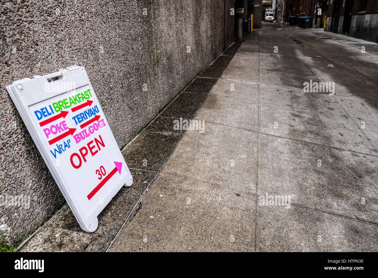 A Deli Sign pointing at scary dark and wet alley Stock Photo