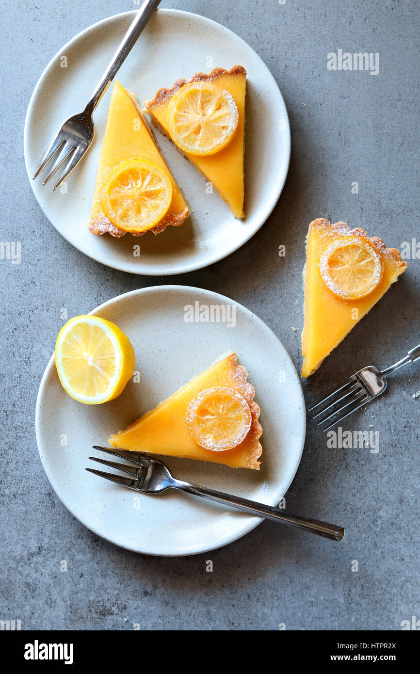 Lemon tart slices served on white plates.Top view - Stock Image