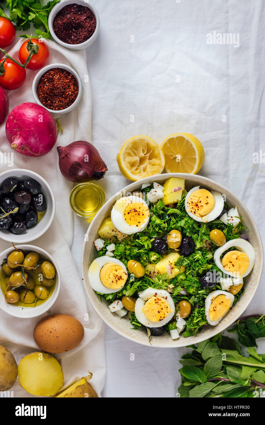 Mediterranean style potato salad with herbs and hard boiled eggs accompanied by black and green olives, red onion, - Stock Image