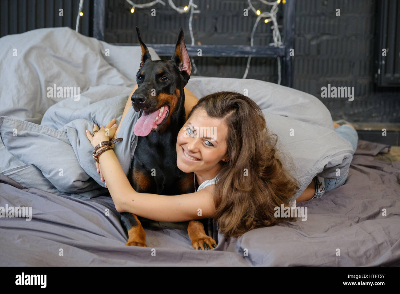 Young pretty woman with black doberman dog in the bed - Stock Image