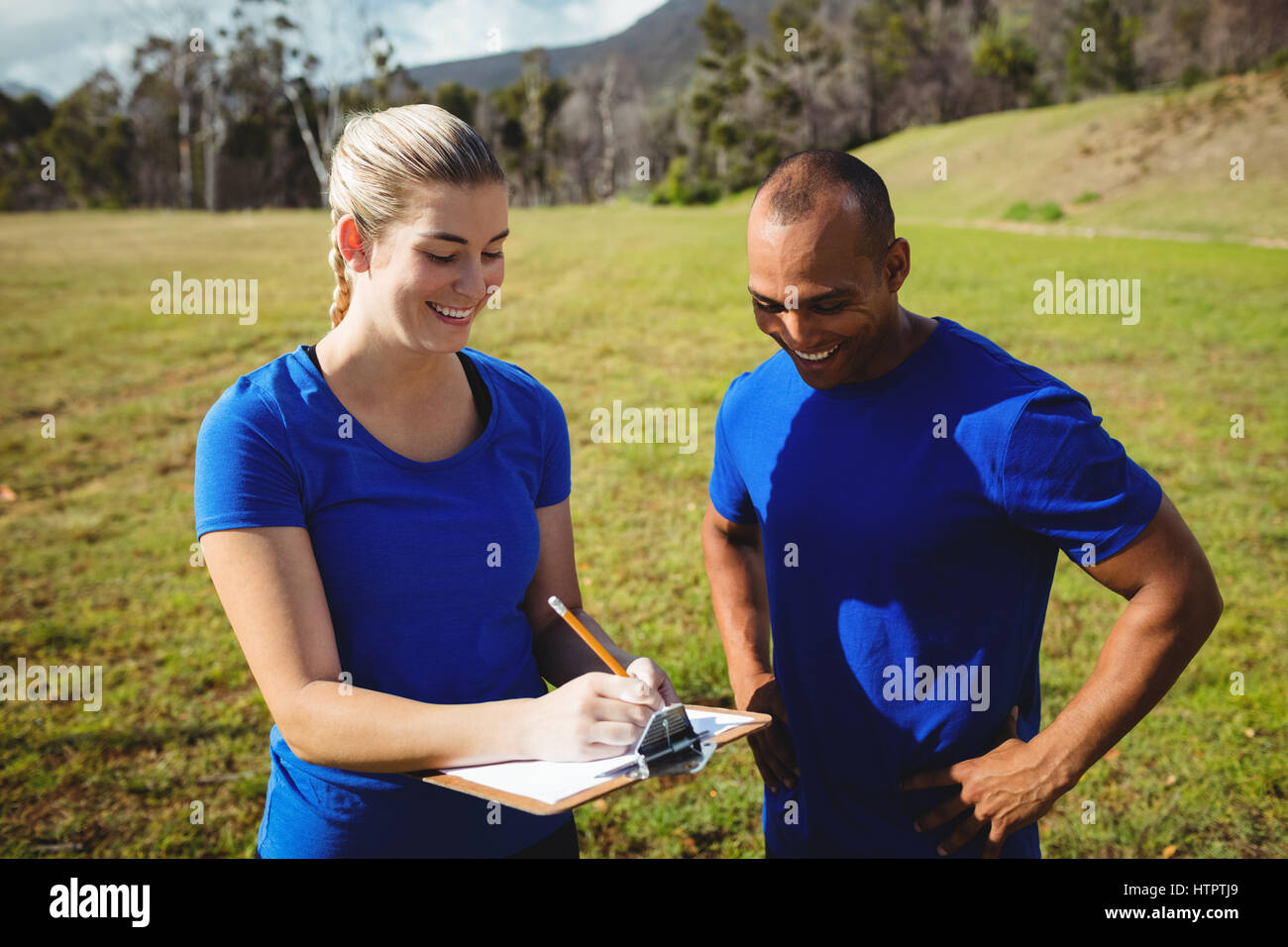 Female trainer instructing a man in bootcamp - Stock Image