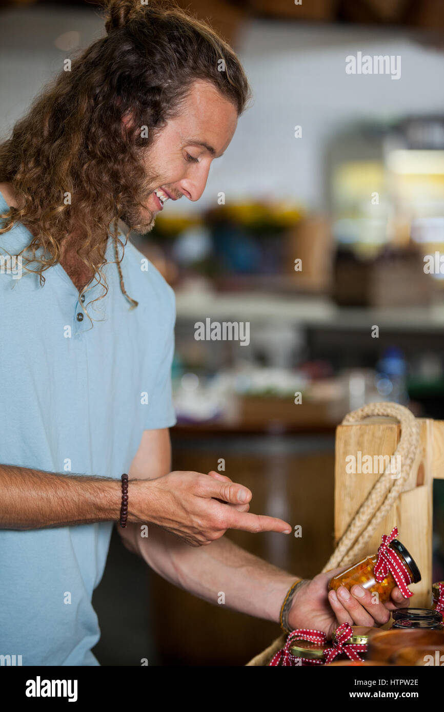 Smiling man looking at pickle in market - Stock Image