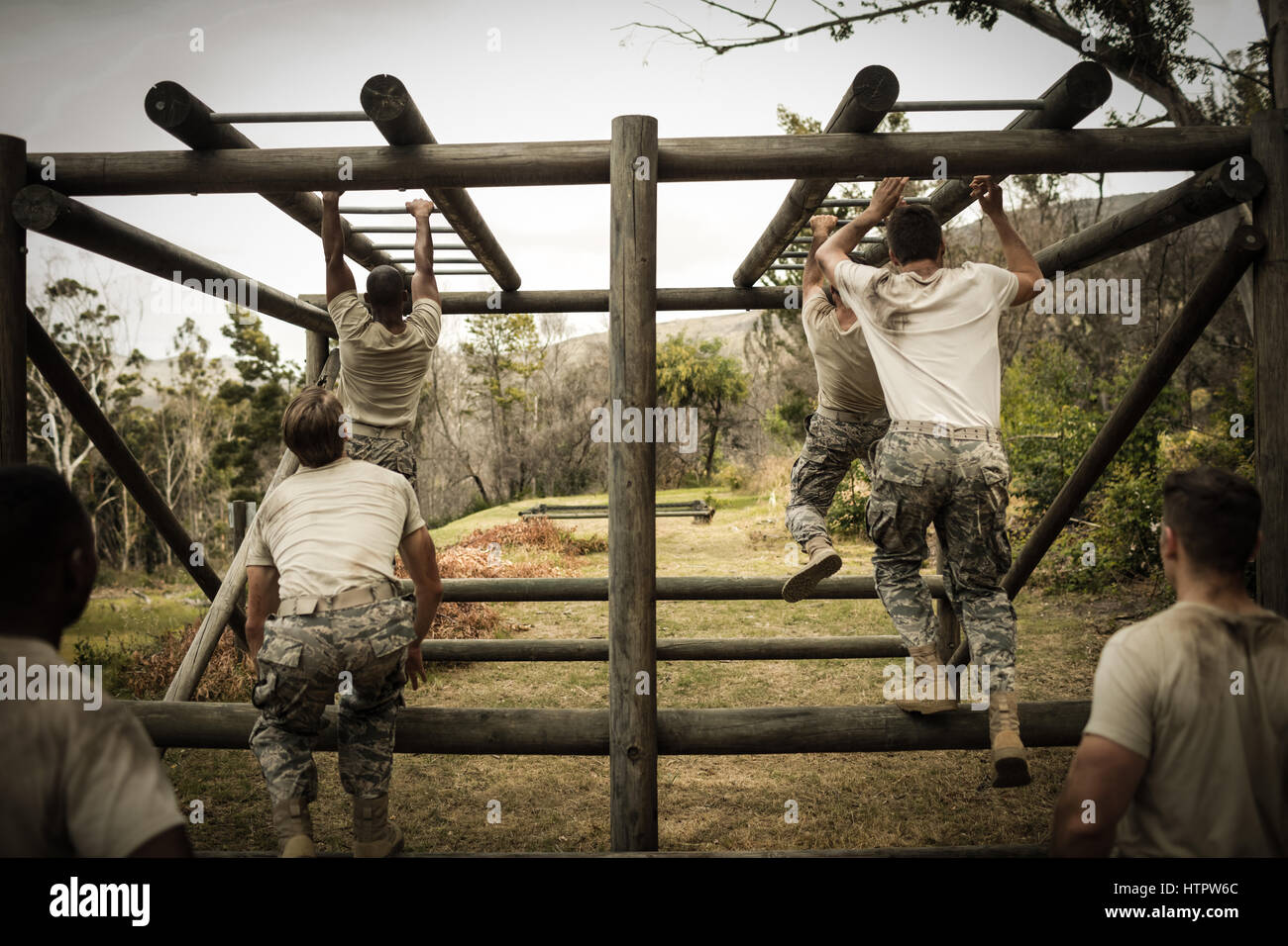 Rear view of soldiers climbing monkey bars - Stock Image