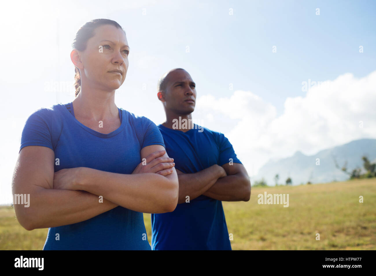 Female trainer and male trainer standing with arms crossed in bootcamp - Stock Image